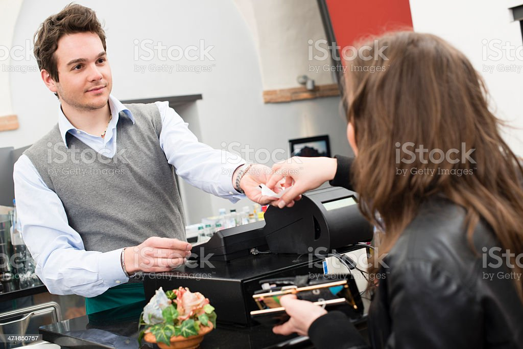 Young woman paying at the restaurant stock photo