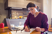 young woman paying bills from home
