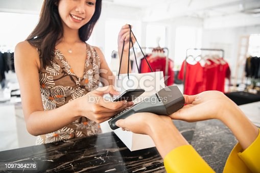 istock Young woman paying contactlessly 1097364276