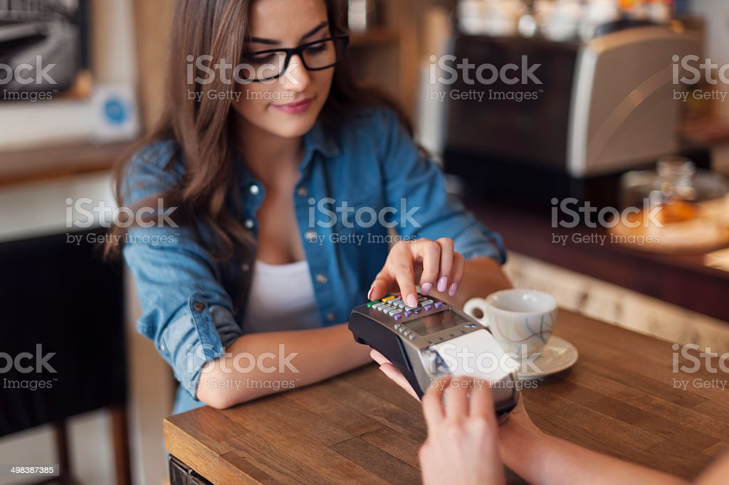 Young woman paying for cafe by credit card reader stock photo