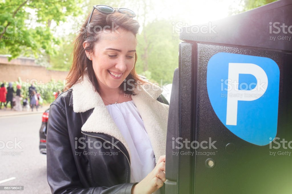Jovem mulher pagando o estacionamento na rua - foto de acervo