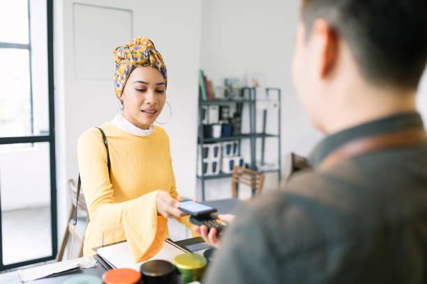 jeune femme payant avec smartphone dans un cafe - business malaysia photos et images de collection