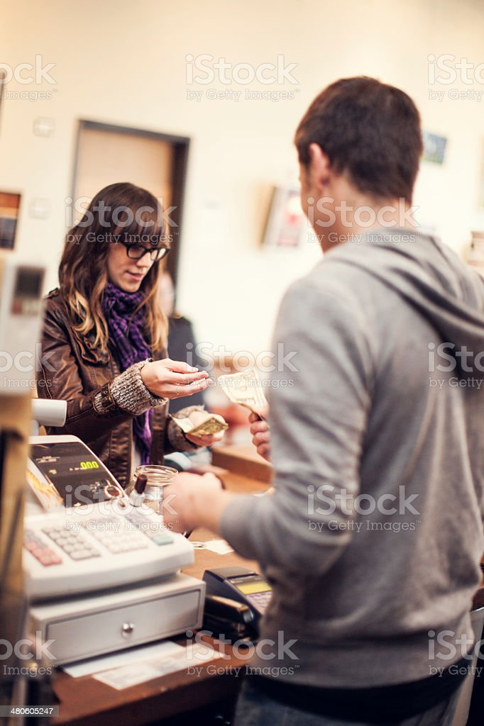 Young woman pays cashier at coffee shop stock photo
