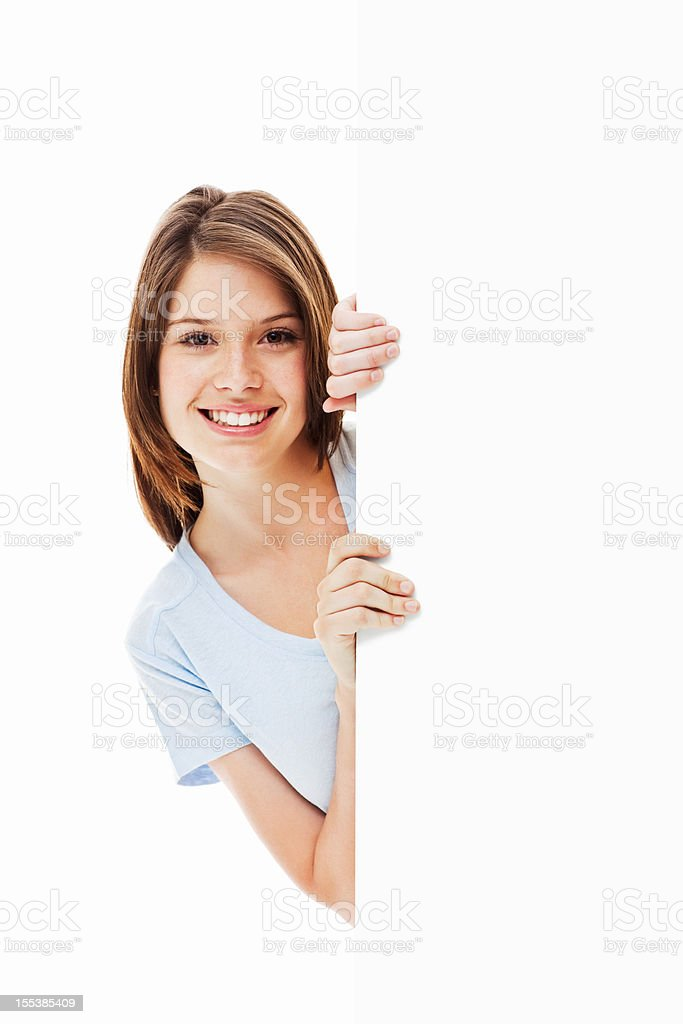 Young Woman Peeking Around a Corner - Isolated stock photo