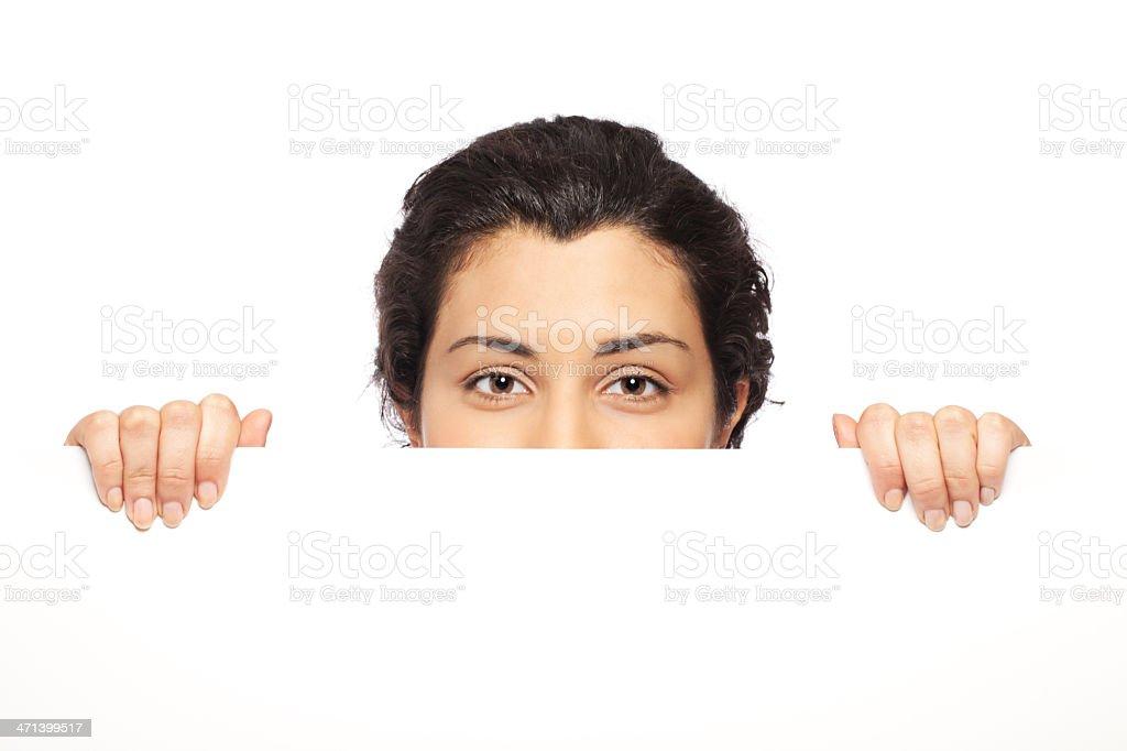 Young woman peeking behind blank sheet royalty-free stock photo