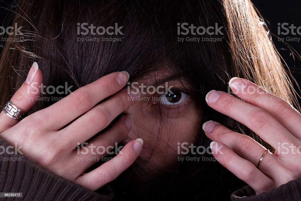 Young woman peeks through her hear royalty-free stock photo