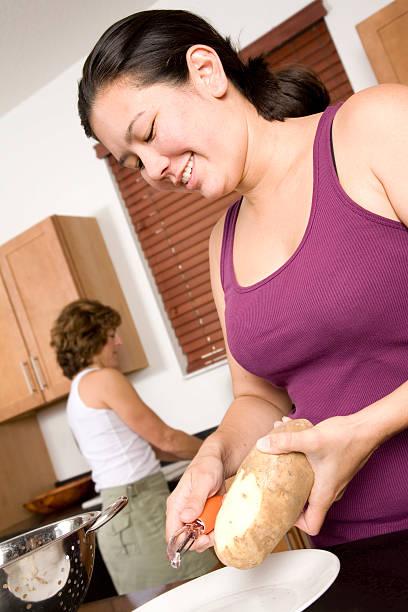 jungen frau schälen einem kartoffel in ihrer küche - peeling zu hause machen stock-fotos und bilder