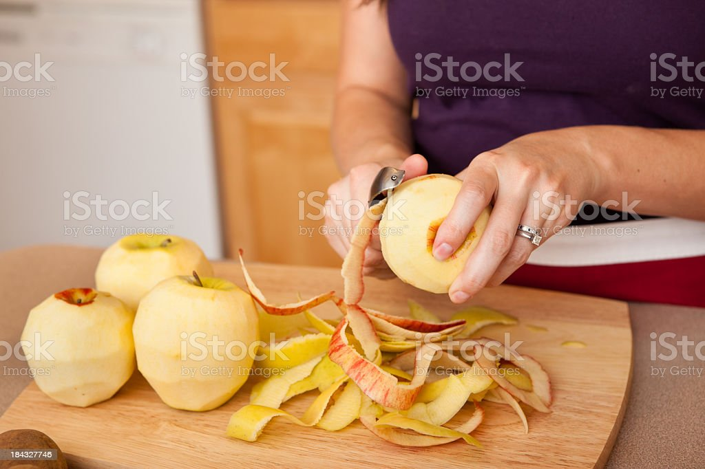 Young Woman Peeling Apples in Kitchen stock photo