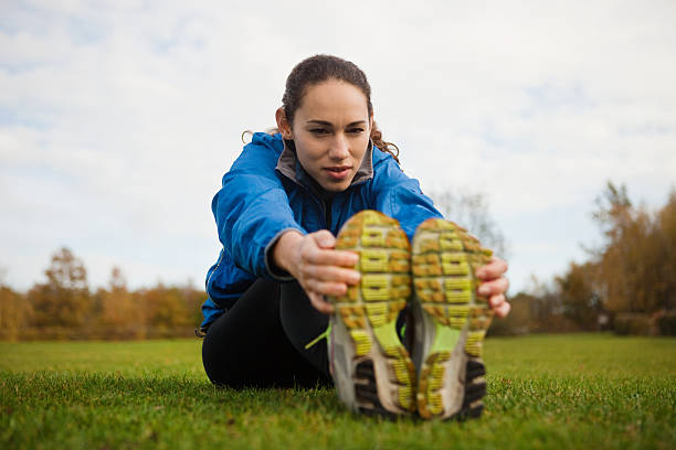 Young woman performing stretches in park  touching toes stock pictures, royalty-free photos & images