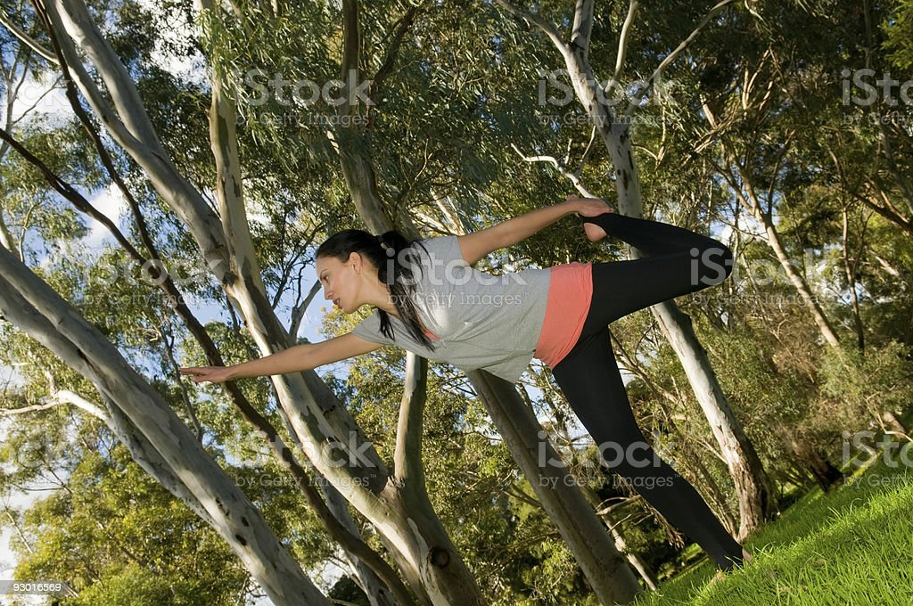 Young woman performing yoga in a park royalty-free stock photo