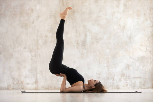 Young woman performs Viparita Karani pose on mat indoors Young sporty woman practising yoga on mat near grunge beige wall studio background, girl performs legs up half candle or Viparita Karani pose exercise, side view, mental physical health care concept shoulder stand stock pictures, royalty-free photos & images