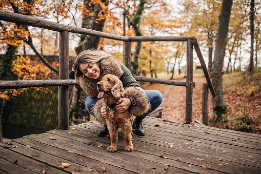 One beautiful young woman petting her happy cocker spaniel dog outside on the porch of log cabin.