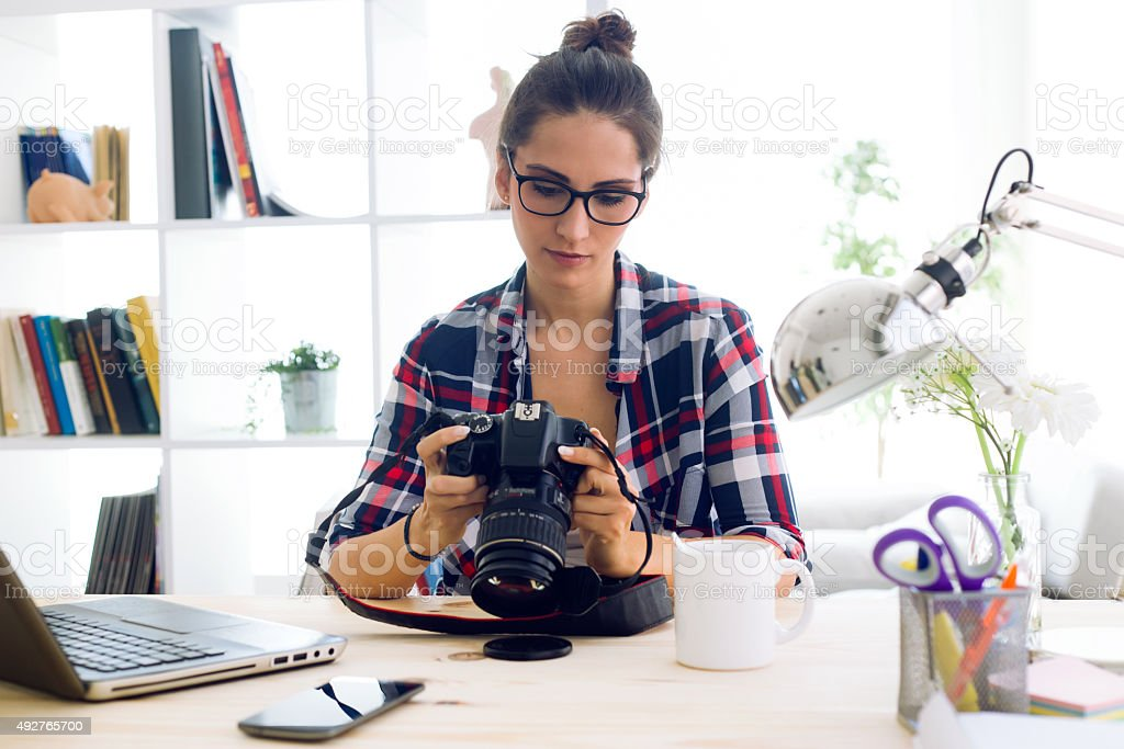 Young woman photographer checking previews on camera in the stud stock photo