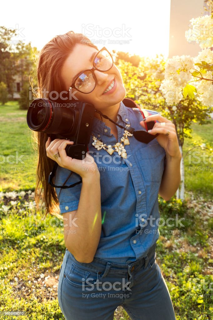 Young woman photographer holding camera outdoors. Happy freelancer taking pictures in park zbiór zdjęć royalty-free