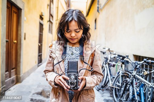 Young woman photographer with a vintage camera in the city