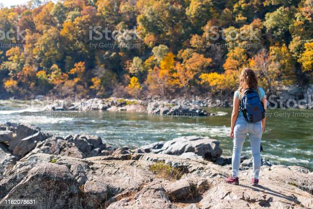 Photo of Young woman photographer with backpack and camera looking at view of Potomac river in Great Falls with autumn colorful foliage in Maryland