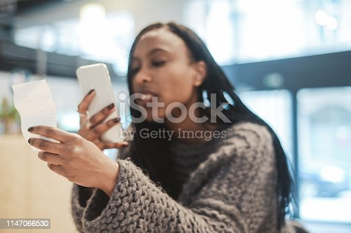 Young woman photographing a receipt in the cafe