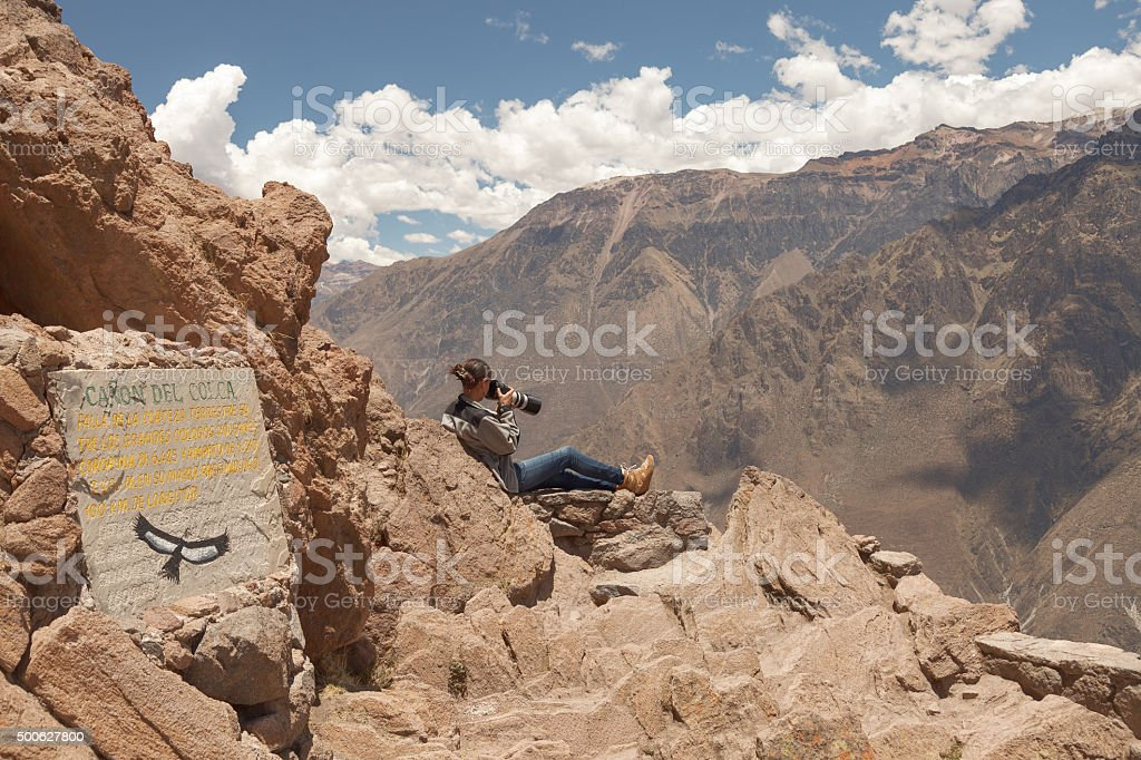 Young woman photographing condors in Colca, Arequipa, Peru stock photo