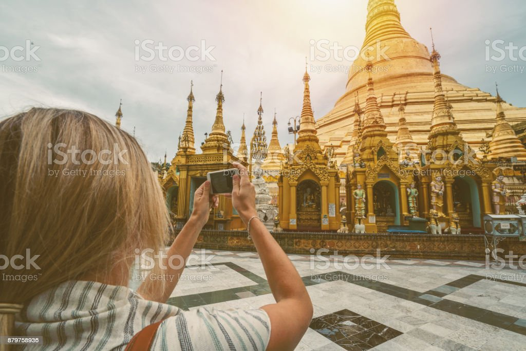 Young woman photographing pagoda with smart phone, Myanmar stock photo