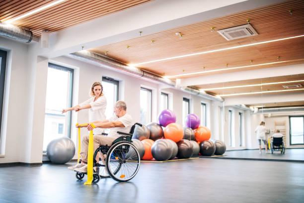 physiothérapeute de jeune femme avec un homme senior en fauteuil roulant. - sports en fauteuil roulant photos et images de collection