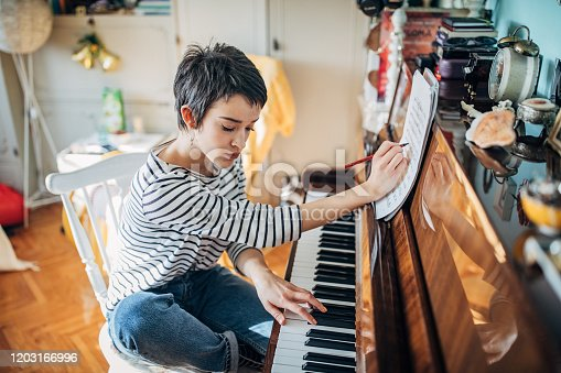 One woman, young woman pianist playing piano and writing musical notes in her room at home alone.