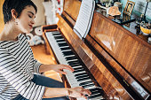 One woman, young woman pianist playing piano in her room at home alone.