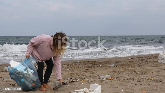 962184460 istock photo Young woman pick up garbage on beach 1186731068