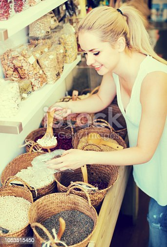 young smiling blonde woman taking dried beans with scoop from basket in food store