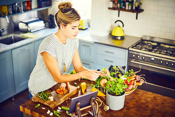 Young woman picking mint leaves at kitchen island stock photo