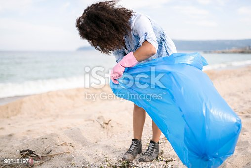 962184460 istock photo Young woman picking up garbage during local clean up 962181974