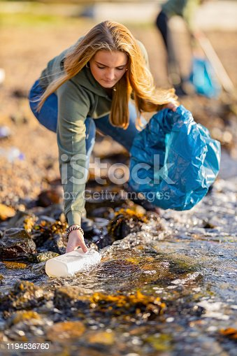 962184460 istock photo Young woman picking up garbage from rocky shore 1194536760