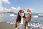ビーチで海のガラスを拾う若い女性