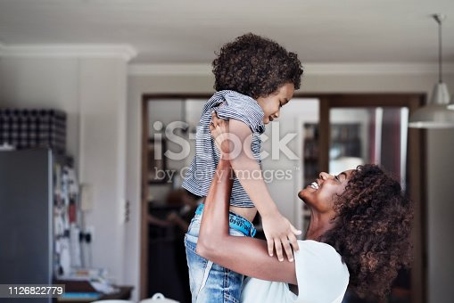 Side view of young woman picking up son at home. Happy mother is playing with boy. Family is wearing casuals.