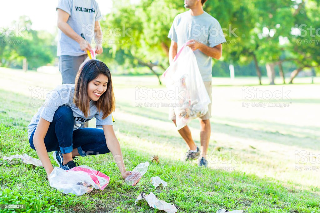 Young woman picks up trash in park Beautiful young Asian woman bends down to pick up trash in the park. Male volunteers pick of trash behind her. They are wearing gray volunteer t-shirts. A Helping Hand Stock Photo