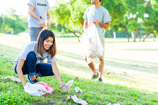 Young woman picks up trash in park Beautiful young Asian woman bends down to pick up trash in the park. Male volunteers pick of trash behind her. They are wearing gray volunteer t-shirts. clean environment stock pictures, royalty-free photos & images