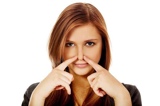 Young woman pinches nose with fingers hands looks Young woman pinches nose with fingers hands looks. human nose stock pictures, royalty-free photos & images
