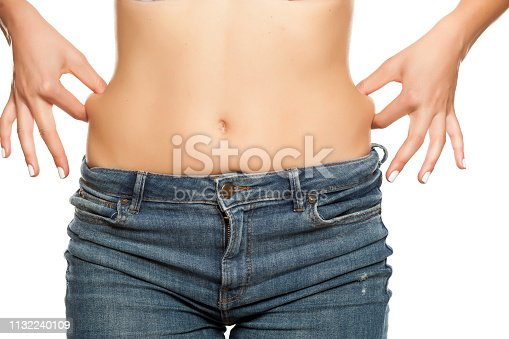 Young woman pinching fat on her waist on a white background