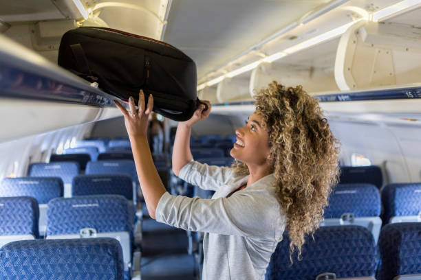 Young woman places luggage in airline overhead bin A smiling young businesswoman stands in the aisle of a commercial airliner and places her carry on bag in the overhead bin. carry on luggage stock pictures, royalty-free photos & images
