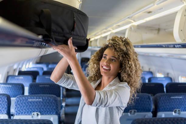 junge frau orte gepäck im gepäckfach in flugzeug - reisegepäck stock-fotos und bilder