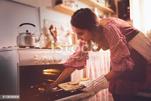Young female baker baking homemade pies in vintage kitchen oven