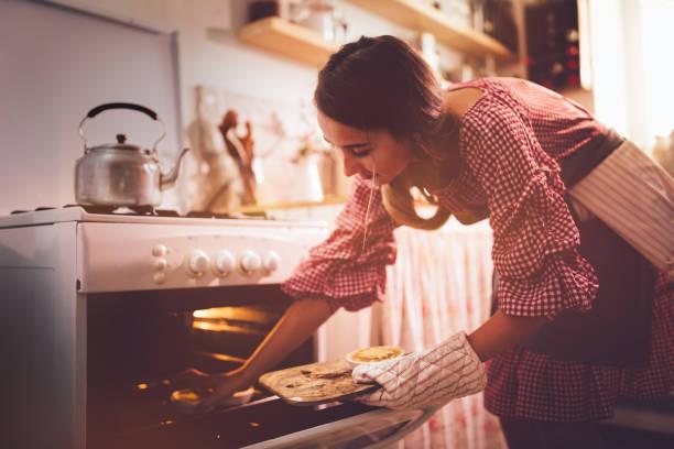 junge frau in küche ofen zum backen von torten platzieren - modetorten stock-fotos und bilder