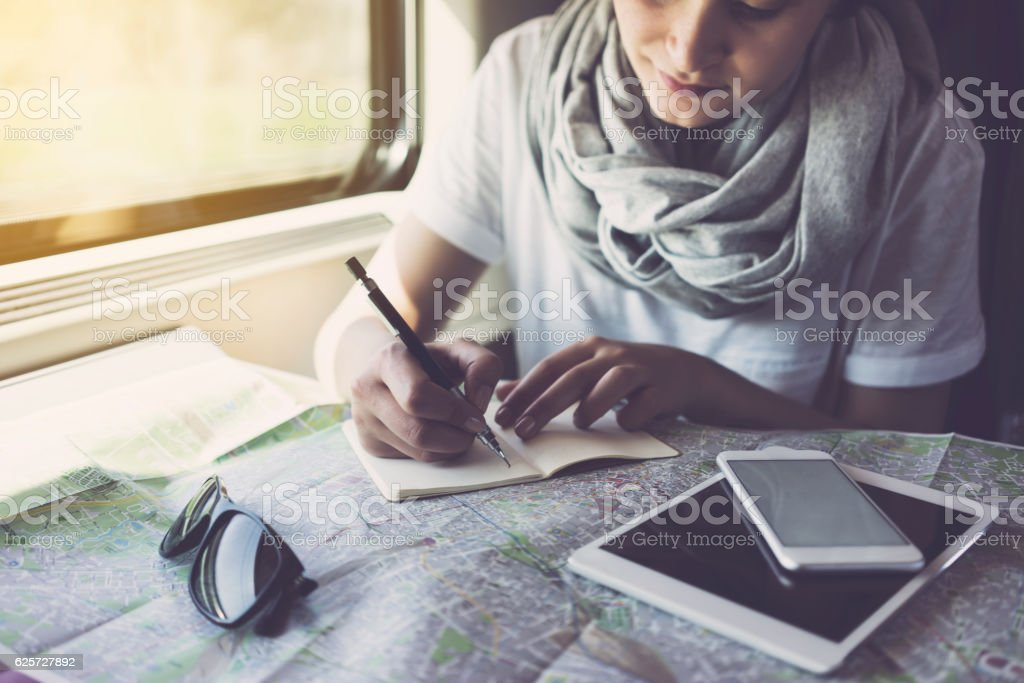 Young woman planning a trip, using smartphone, travelling by train stock photo