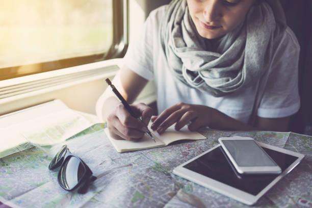 young woman planning a trip, using smartphone, travelling by train - bahn reisen stock-fotos und bilder