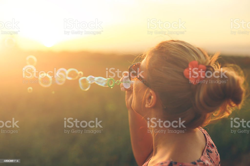 Young woman playfully blowing soap bubbles stock photo