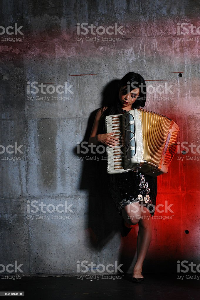 Young Woman Playing Accordian Against Cement Wall stock photo