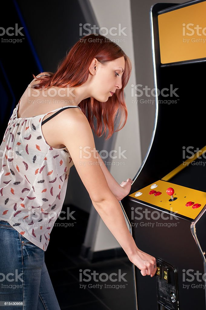 Young woman playing arcade stock photo