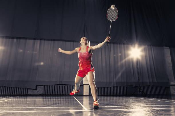 Jeune femme jouer au badminton au gymnase - Photo