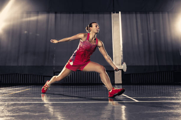 Young woman playing badminton at gym Young woman playing badminton over gym background badminton stock pictures, royalty-free photos & images