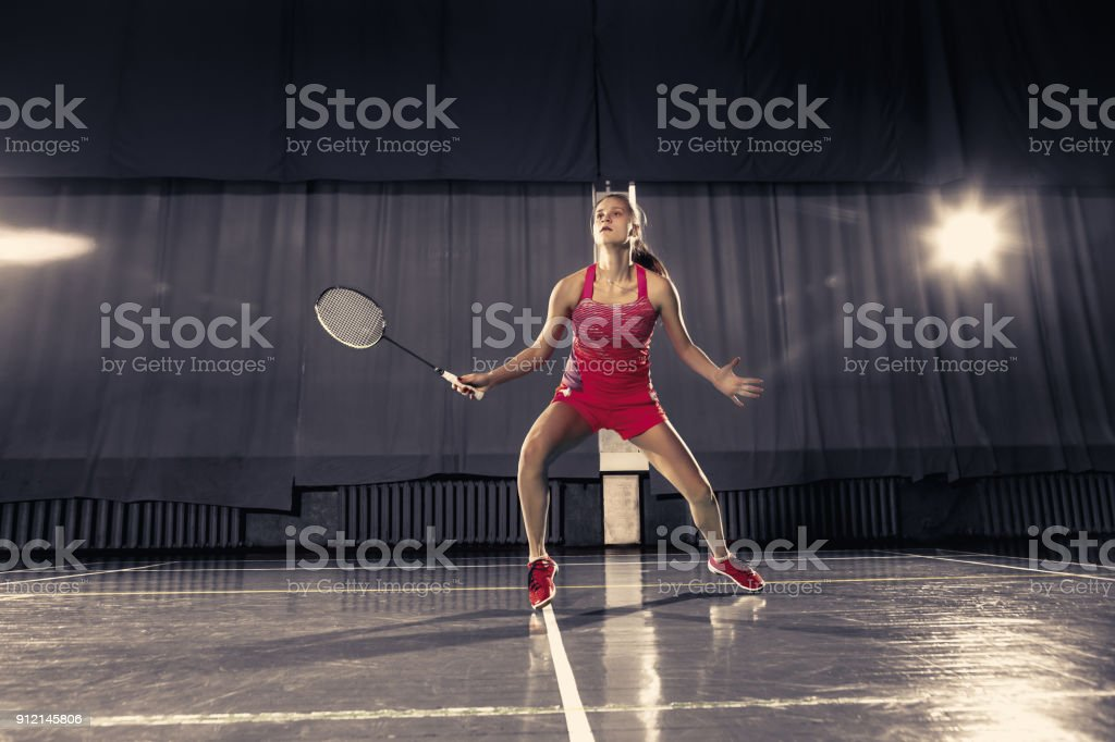 Young woman playing badminton at gym stock photo