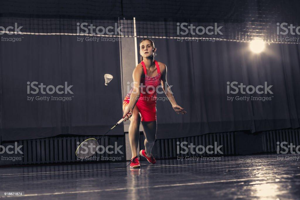 Mujer joven jugando a badminton en el gimnasio - foto de stock